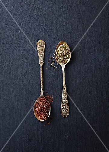 Dried green and red rooibos tea on spoons