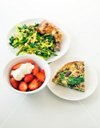 A healthy meal of chicken, vegetables, frittata and strawberries