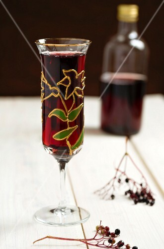 Elderberry juice in a glass and a bottle