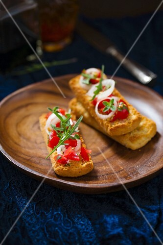 Bruschetta topped with tomatoes, onions, marjoram and rocket