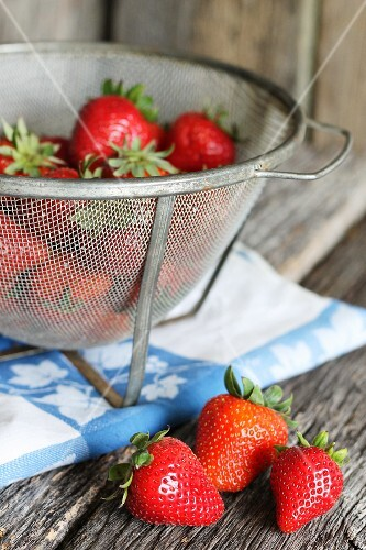 Fresh strawberries in a metal sieve on a wooden table and next to it