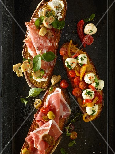 Bruschetta topped with tomatoes, fresh herbs, salami, prosciutto and mozzarella