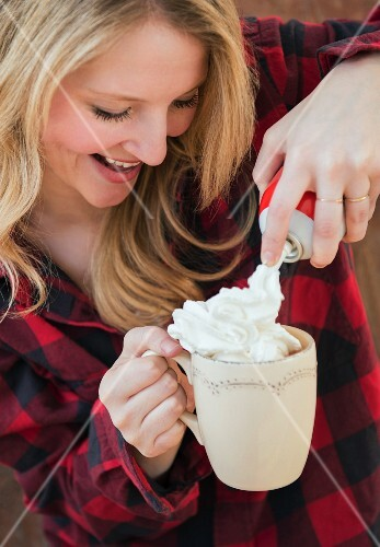 A young woman squirting cream onto a cup of hot chocolate