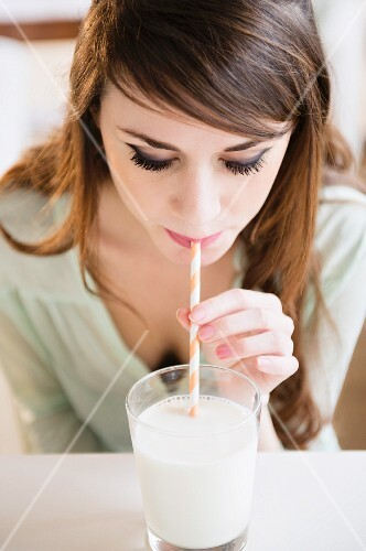 Young woman drinking milk through a straw