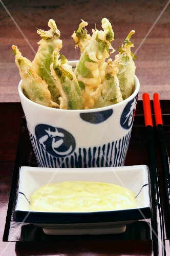 Pea pod tempura with a dipping sauce served in oriental crockery