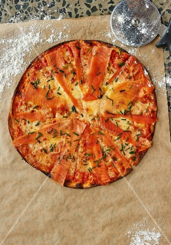 Salmon pizza on a piece of baking paper (seen from above)