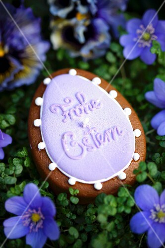 An egg-shaped candle with the words 'Frohe Ostern' surrounded by liverwort floweers