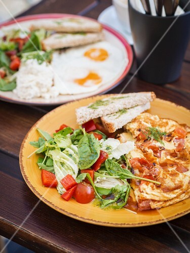 A healthy breakfast featuring crêpes, salad, fried egg and toast