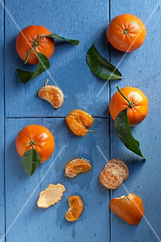 Clementines with leaves, whole and peeled