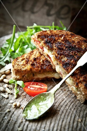 A grilled sandwich with tomatoes, basil and mozzarella