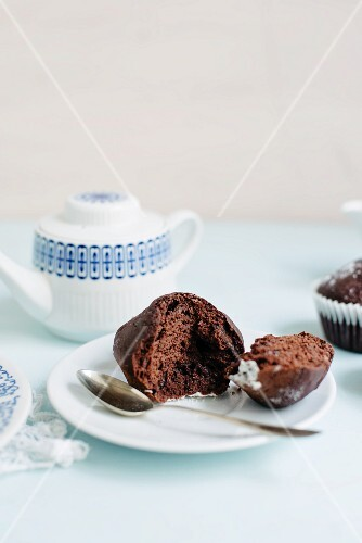 A broken chocolate muffin served with tea