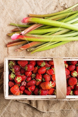 Strawberries in a wooden basket next to rhubarb