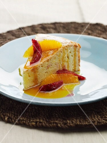 A slice of cake with blood oranges, orange and citrus fruit sauce