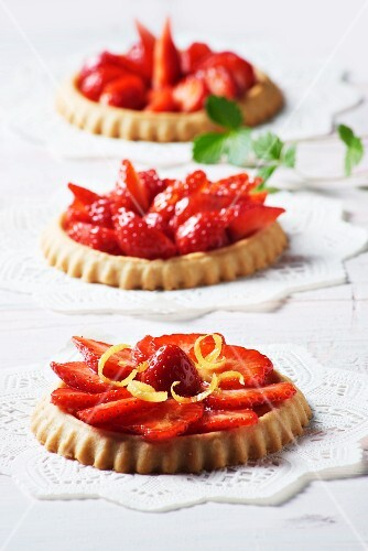 Three strawberry tartlets with lemon zest on doilies