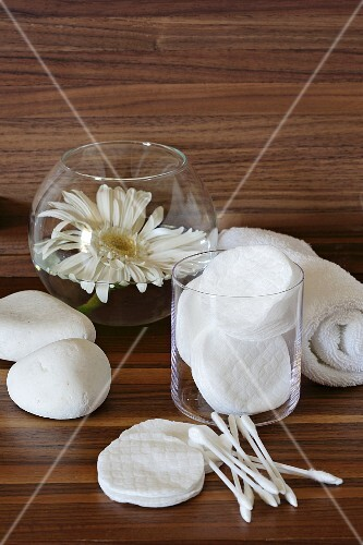 Cotton pads, cotton buds, a hand towel and a white gerbera in a glass of water