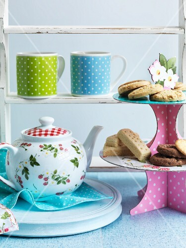 Colourful tea crockery and biscuits on a unique cake stand