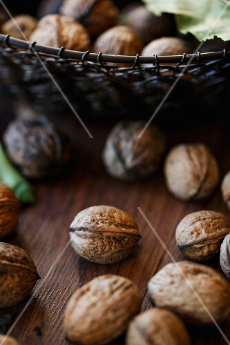 Walnuts on a wooden surface and in a wire basket