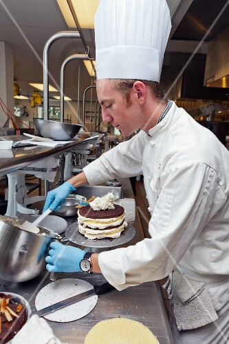 A chef decorating a layer cake with frosting