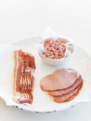 Rashers and slices of bacon and diced bacon on parchment paper