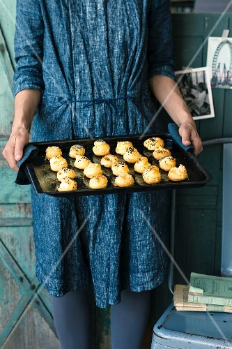 A woman holding a baking tray of gougeres (cheese profiteroles, France)