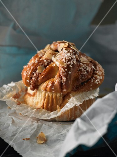 A cinnamon bun with sugar nibs and flaked almonds