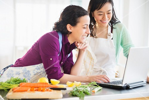 Two women using a laptop and cooking together