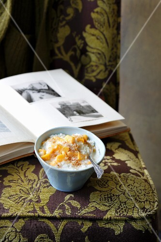 Coconut rice pudding with mango on an upholstered chair in front of a photo album