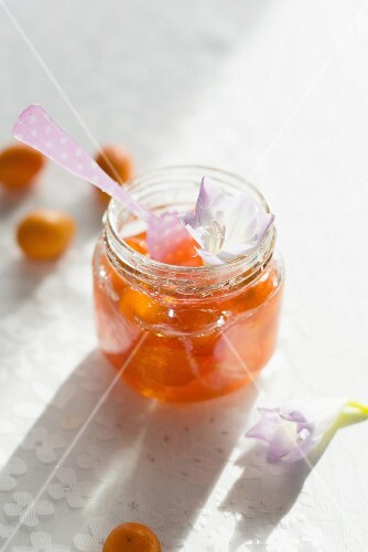 A jar of kumquat jam with a spoon