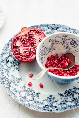 Half a pomegranate and pomegranate seeds in vintage plate