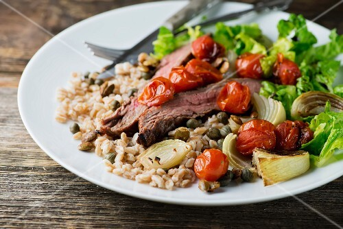 Grain salad with beef steak and oven-roasted vegetables