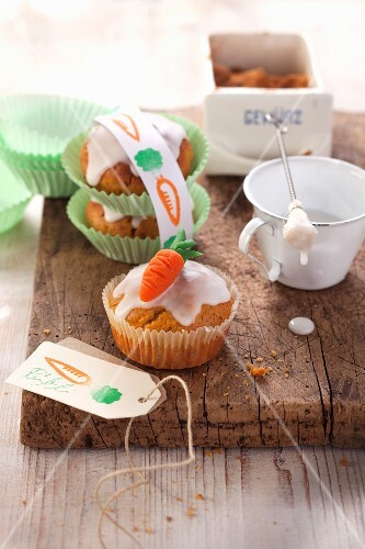 Carrot cake muffins with icing sugar and marzipan carrots