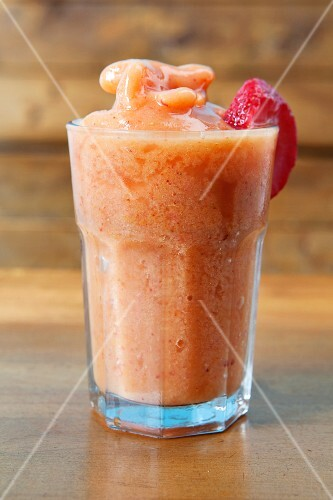 A peach smoothie made with apple juice, oranges and strawberries