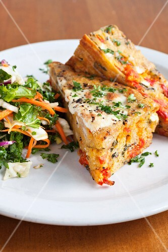 Panini with tomatoes, mozzarella, egg, parsley and a side salad