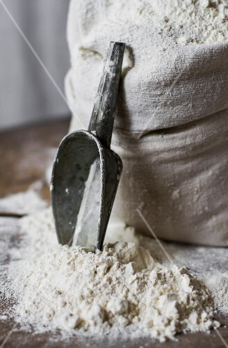 A pile of flour and a scoop next to a sack of flour