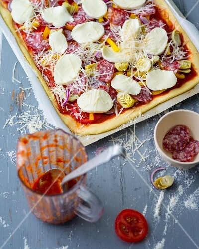 Pizza with vegetables, salami and mozzarella being made