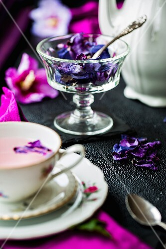 Dried hibiscus petals in a glass bowl, a teapot and a cup of hibiscus flower tea