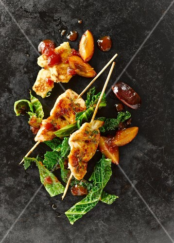 Chicken breast skewers with savoy cabbage, plums, bacon, shredded herb pancakes and tomato sauce
