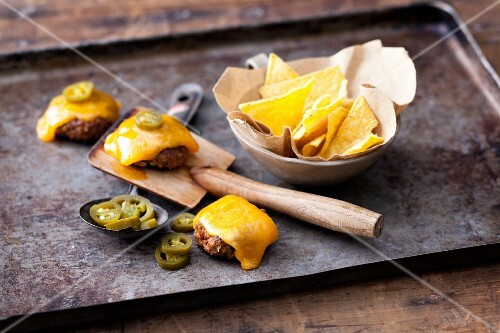 Cheddar raclette with mini chilli burgers, tortilla chips and jalapeños