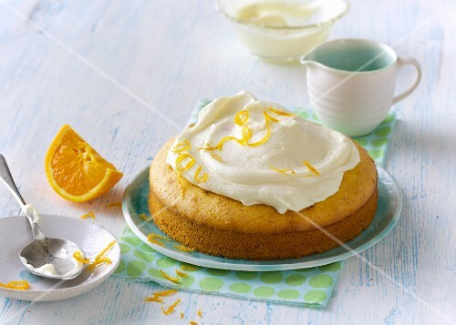 A mini orange cake topped with cream cheese