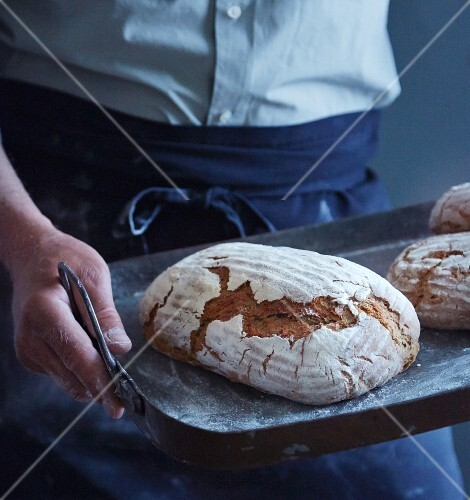 A man holding a baking tray of freshly baked bread