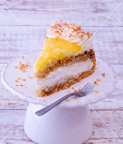 A slice of pineapple cake with cream on a cake stand