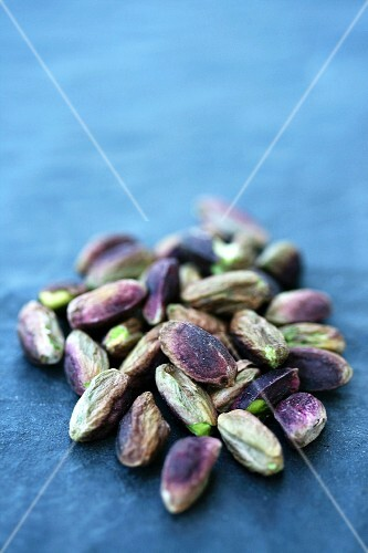 Shelled pistachio nuts on a blue surface