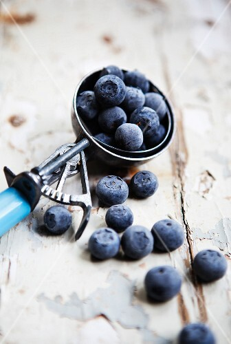 Blueberries in an ice cream scoop on a rustic wooden surface