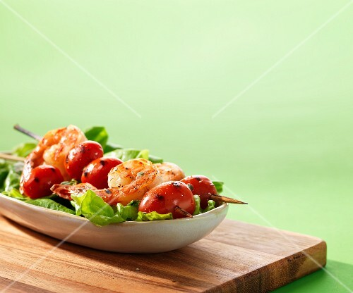Prawn skewers with tomatoes on a bed of lettuce