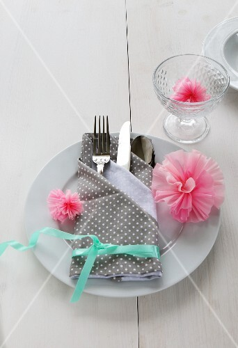 A place setting with a napkin folded as a cutlery bag decorated with paper carnations