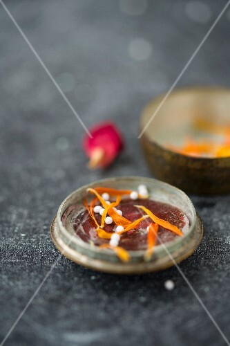 Globules in the lid of an old pill tin with dried marigold petals and a dried rose petal