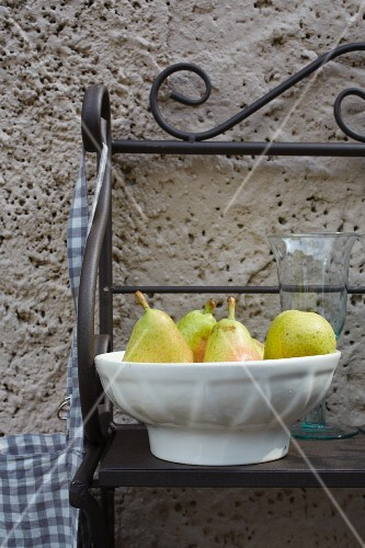 Pears in a bowl against a wall