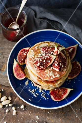 A stack of pancakes with figs and chopped almonds