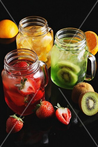 Various types of fruit juice with fresh fruits in glass jars
