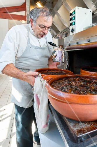 A chef removing finished cassoulets from the oven